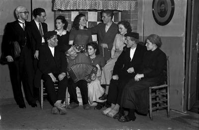 Een groepsfoto een gezelschap voor de schouw; in het midden een accordeonist, links een verkleed persoon. Weet iemand wie dit zijn en ter gelegenheid waarvan deze foto is           gemaakt?