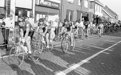 Het peloton dendert over de Hoofdstraat in Schijndel. Joop Zoetemelk rijdt in de gele trui op positie zes en voor hem rijdt toenmalig Duits kampioen Gregor Braun. De Raleigh           renner is vermoedelijk Aad van den Hoek. (Zie ook: https://www.bhic.nl/ontdekken/verhalen/eerst-de-tour-de-france-winnen-dan-naar-de-lus-van-schijndel)