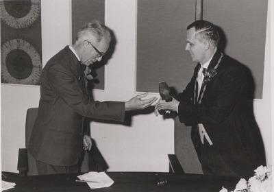 Commissaris C. Kortmann overhandigt burgemeester baron Van Hövel tot Westerflier een voorzittershamer als geschenk vanwege de opening van het nieuwe           gemeentehuis.