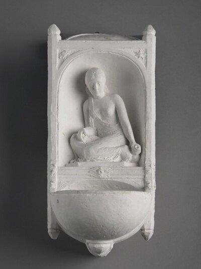 Fonteintje met nis, waarin een geknield gezeten vrouw met in de linker hand een kruik. En face.