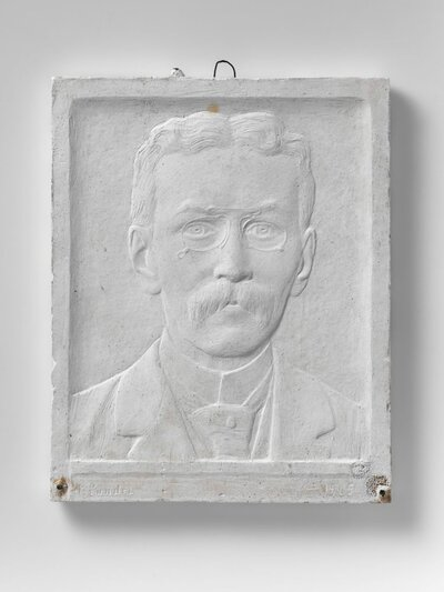 Portret van een man met bril, snor en openstaande boord. Scheiding in het midden, en face.