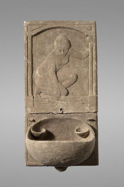 Fonteintje met afbeelding van een geknield gezeten vrouw met in de linker hand een kruik. En face.