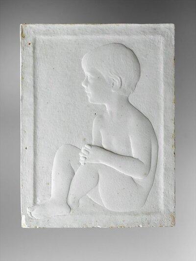 Naar links gezeten naakte jongen en profile, met de handen gevouwen op de opgetrokken knieën.