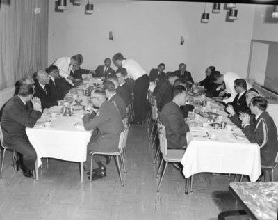 Een delegatie van de Ministerraad brengt een bezoek aan de 3e groep Geleide Wapens (3 GGW) in Blomberg.Hier gebruikt het gezelschap de lunch met aan het hoofd van           de tafel rechts luitenant-generaal A.B. Wolff (BDL) met links minister van Defensie P. de Jong.Aan de rechtertafel vooraan rechts de adjudant van de BDL kapitein-vlieger J.J.           Françoijs.