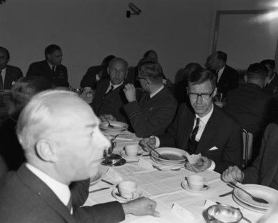 Een delegatie van de Ministerraad brengt een bezoek aan de 3e groep Geleide Wapens (3 GGW) in Blomberg.Hier gebruikt het gezelschap de           lunch.Links minister-president J.M.L.Th. Cals met de commandant van 3 GGW luitenant-kolonel W. Bartelings, daarnaast 2e van links minister van Defensie P. de Jong en de           BDL luitenant-generaal A.B. Wolff.Vierde van rechts minister J. den Uijl.