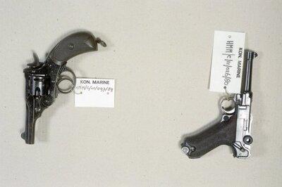 Wapencollectie van het Helders Marinemuseum.Links: Revolver, 'Webley Mk. II', kaliber 11.4 mm. Een zesschots revolver met neerklapbare loop en           automatische stervormige uitwerper.Rechts:Pistool, 'Parabellum M.1908', kaliber 9 mm. Semiautomatisch pistool met een magazijn voor 8 patronen. Het laden van           de patronen via het zogenoemde knokkelsysteem.