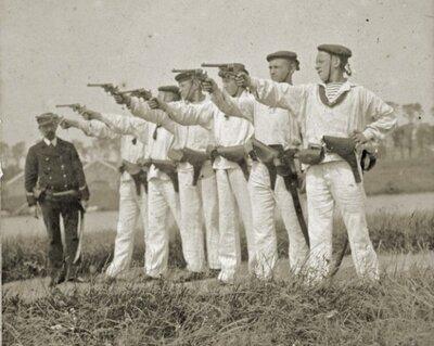 Matrozen van een Nederlands oorlogsschip krijgen les vuistvuurwapens van een onderofficier-konstabel op Curacao.