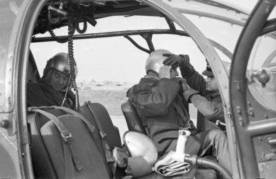 Een delegatie van de Ministerraad brengt een bezoek aan de 3e groep Geleide Wapens (3 GGW) in Blomberg.Minister van Defensie P. de Jong zit achterin de Alouette II           helikopter en op de voorstoel wordt minister-president Cals geholpen met het opzetten van de vliegerhelm. De foto is gemaakt op vliegbasis Ypenburg voor vertrek naar           Blomberg.