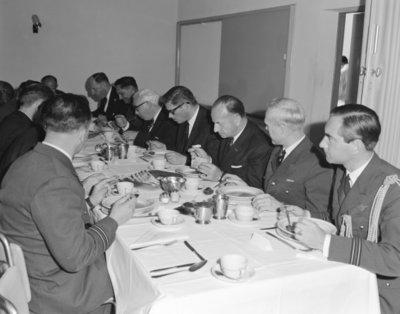Een delegatie van de Ministerraad brengt een bezoek aan de 3e groep Geleide Wapens (3 GGW) in Blomberg.Hier gebruikt het gezelschap de           lunch.Geheel rechts kapitein-vlieger J.J. Françoijs, adjudant van de BDL.