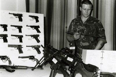 Een onder-officier/ wapeninstructeur geeft uitleg over verschilliende soorten kleine en grote handvuurwapens. Rechts liggen een Minimi, een MAG en een Brengun. Op de           achtergrond zijn verschillende pistolen en revolvers zichtbaar.