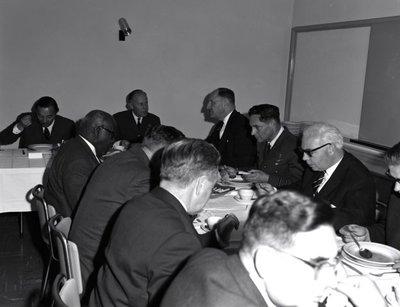 Een delegatie van de Ministerraad brengt een bezoek aan de 3e groep Geleide Wapens (3 GGW) in Blomberg.Hier gebruikt het gezelschap de lunch met aan het hoofd van           de tafel rechts luitenant-generaal A.B. Wolff (BDL) met links minister van Defensie P. de Jong en rechts minister van Buitenlandse Zaken mr. J. Luns.