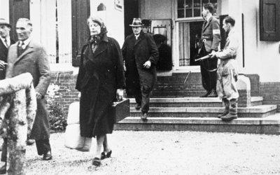 Gearresteerde NSB-ers worden weggevoerd uit het hotel aan de Bloemendaalseweg tegenover waar het oude raadhuis stond.