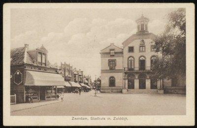 Gemeentehuis Zaandam staat bekend als De Burcht. Rijksmonument in neoclasisistische stijl. Bouw 1846-1847, architect W.A. Scholten. Tegenwoordig in gebruik als kantoorpand. Links:           winkel Goud, Zilver en Uurwerken.