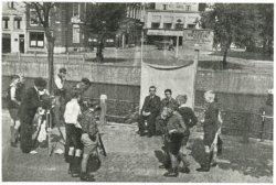 Als gevolg van de verplichte aanschaf van een Persoonsbewijs (PB) in mei 1940, moesten vele burgers pasfoto's laten maken. Hier gebeurt dat in de openlucht op de Lange           Haven, vlak bij cafe De Unie. Het witte pand op de achtergrond is van De Kaplaars, hoek Hoogstraat/Koemarkt (Broersvest).