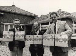 Collectanten van het Rode Kruis afdeling Schiedam, voor hun pand, de voormalige kleuterschool KiVeVa (Kinderen Van één Vader) in de Van Beverenstraat. Links Gerrit van           Aalten, rechts Henk van Deursen. De naam van de middelste persoon is onbekend.