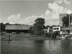 De Houthaven van Van de Wetering gezien vanaf de Westerhavenbrug in de richting van de houtloodsen. Rechts het witte gebouwtje is het kantoor van de Schiedamse Transport en           Expeditie Maatschappij. Weer rechts daarvan een gedeelte van de Wasserij De Pauw / Nico Nijman aan de Stadhouderslaan. Op de achtergrond een gedeelte van de hoogbouw van Huize Francois           Haverschmidt.