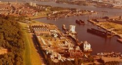 De Wilhelminahaven met de werf van de Hollandse Constuctie Groep met twee pontons waarop twee modulen voor een booreiland. Links op de achtergrond de woonwijk Gorzen met de           flats aan de Havendijk. Rechts boven de bedrijfsterreinen van de Rotterdamse Droogdok Maatschappij.