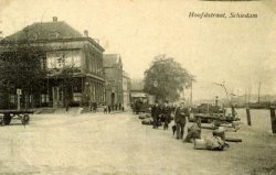 Op de voorgrond een deel van het Hoofdplein en in het verlengde daarvan de Hoofdstraat. Links café 'De Maas', rechts de Voorhaven, alles gezien vanaf het Hoofdplein. Let op           de paardentram die sinds 1902 de route van het Stationsplein naar het Hoofdplein rijdt.