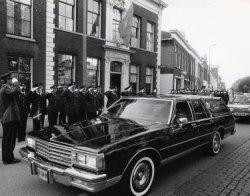 De lijkstoet met het stoffelijk overschot van commissaris C. van der Haagen passeert hier het Hoofdbureau van Politie aan de Lange Nieuwstraat. Van der Haagen was vanaf 1967           tot zijn overlijden bij de Schiedamse Gemeentepolitie betrokken.