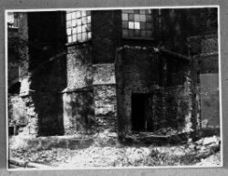 Buitenzijde van het middenkoor, gezien vanuit het Noord-Oosten. De voormalige sacristie (later leerkamer, later kerkkantoor) tegen de Oostelijke muur van de Noordkerk is           weggebroken. De muuropening vormde de toegang van deze sacristie tot het middenkoor.