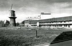 De bouw van nieuwe woningen aan de Sint Anna Zusterstraat, gezien vanaf het Groenweegje. Links van de woningen de voormalige mouterij van Bols en De Koning, later bekend als           De Goudsbloem en weer later Restaurant de Mouterij. In molen De Noord wordt Restaurant de Noordmolen gevestigd. De voormalige Bols-silo staat te huur.