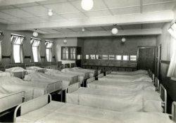 De slaapzaal van de kleine meisjes van de op 25 februari 1933 geopende meisjesafdeling van het R.K. Weeshuis aan de Hoogstraat.