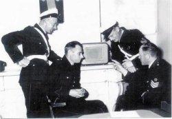 De Verkeersdienst van het gemeentelijk politiekorps luistert naar een uitzending van de Schiedamse Radio Centrale (distributieradio). Van links naar rechts: Paul de Heer, Jo           Krowinkel, Henk Karel en Jan Frijters.