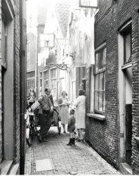 In de Prinsensteeg staat bakkersknecht/broodbezorger Venzelaar van Bakkerij Van der Staaij met zijn geldtas en leunend op de bakkerswagen. Op de achtergrond staat Toos van           Dooren-Venzelaar met dochter Anneke achterop de fiets. In de deuropening staat Wil Venzelaar, zus van Toos. De vrouw op de rug gezien is mevrouw Huiskens. De vrouw met de wol in haar handen           is de schoondochter van mevrouw Huiskens.