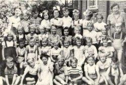 Een klassenfoto van de Prinses Julianaschool in de Oostsingel, met juffrouw Groeneweg. Een naamlijst en nummering van de personen is te vinden in de map aan de balie van de           studiezaal.