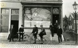 Café Maaszicht in de Hoofdstraat, tussen Hoofdplein en Havendijk. Let op de heren op de tandem en de twee mannen met een glas bier in de hand op het trapje voor de           café-entree.