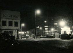 Gezicht op de Koemarkt vanaf de hoek met de Lange Haven in de richting van de Hoogstraat (voor het witte pand van schoenenzaak De Kaplaars naar links), de Broersvest met           café 't Vierkantje en op de achtergrond de flat Singelwijck (met verlichte ramen)