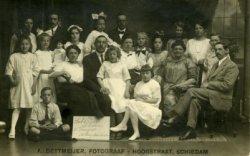 Een groepsfoto van leden van het Subcomité Schiedam ter verzorging van Oostenrijkse arbeiderskinderen, die samen met de Oostenrijkse kinderen van het tweede transport op de           foto staan. Links boven het bord zit mevrouw E. Koeten-Ooms, rechts de heer A. van Duinhoven. Op de foto staan ook Piet van Ruiven en mevrouw Rieken-Ooms.