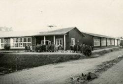 Een zogeheten Finse houten schoolgebouw gezien vanaf het Lorentzplein. De Finse school is een houten gebouw dat in de jaren 1948-1950 overal in Nederland werd gebouwd. Het           hout kwam uit Finland in verband met een een handelsovereenkomst met dat land, hetgeen al snel de naam 'Finse School' tot gevolg had. Rechts zo'n school in de Fahrenheitstraat. Het in 1949           geplaatste gebouw biedt huisvesting aan de Prof. Dr. Kohnstammschool.