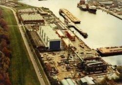 Luchtfoto van het bedrijf de Hollandse Constructie Groep (HCG) aan de Wilhelminahaven. De weg links met de rij geparkeerde auto's van de werknemers, is de           Westfrankelandsedijk met geheel linksboven zwembad Zuid. Rechts van de Wilhelminahaven de scheepswerf Nieuwe Waterweg.