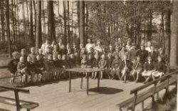 Kinderen in Groot Dennenlust bij de melkbank. Hier werd bij mooi weer om 11.00 uur melk gedronken. Achter de kinderen staan de leidsters en directie. In het midden met           donker haar de directrice F.G. (Femmy) Kerkhoff en helemaal rechts zuster N.Korf.