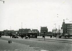De Broersvest en Koemarktplein, gezien vanaf de Rotterdamsedijk (voorgrond). In het midden het tramhuisje omdat hier het eindpunt (keerlus) van de tram naar en van Rotterdam           ligt. De huizen aan de Broersvest zoals De Amstelbron en de panden ernaast liggen lager dan de (enige jaren daarvoor) opgehoogde Rotterdamsedijk en Koemarktplein. De Amstelbron werd later           (1936?) opgevijzeld en de huisjes rechts en deels links daarvan - tot het toen vrij nieuwe pand van de Passage (met Tuschinsky's Passagetheater) - werden afgebroken en door nieuwbouw           vervangen.
