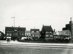 Vanaf de Rotterdamsedijk gezicht op de Broersvest met links de hoek met de Hoogstraat, omstreeks 1935. Rechts, met torentje, een gedeelte van de Passage. Het hoge pand           rechts van het midden is café De Amstelbron.