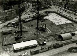 De bouw van o.a. een nieuwe VSB-bank (later Fortis) aan de Broersvest , rechtsboven) bij het Emmaplein. Op de voorgrond - waar de bouwketen staan - de Huis te Riviereweg (al           afgesloten). Ongeveer op die plaats zal later het Stadserf verrijzen. De foto is gemaakt vanaf het Stadskantoor. Linksboven waar de rijen auto's staan is de Singel.