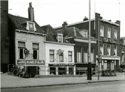 Vier panden aan de westzijde van de Broersvest tussen de Passage (links nog juist zichtbaar) en café Riton: bode J. Stokhof (hier staat C. op het reclamebord), café De           Bushalte, slager Van der Geer.