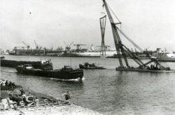 Het transport van het kunstwerk Eurobaak naar de Maasboulevard, waar het geplaatst gaat worden bij Café- Restaurant Europoort. Op de achtergrond het SS Rotterdam in aanbouw           bij de Rotterdamsche Droogdok Maatschappij.