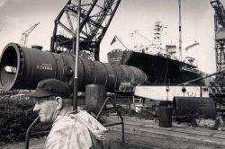 Het transport van een op het bedrijfs gebouwde destillatiekolom op de werf van de N.V. Dok- en Werfmaatschappij Wilton-Fijenoord.
