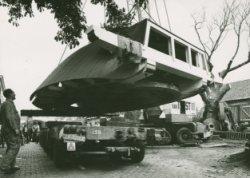 Het transport van een nieuwe molenkap gemaakt bij de molenmakerij van Van der Loo, wordt op een dieplader geplaatst om naar Maassluis te worden vervoerd.