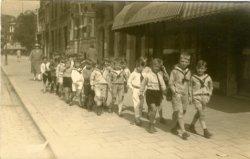 Een schoolklas aan de wandel, mogelijk in Rotterdam. De jongen in de lange witte broek is Ary Marie Dettmeijer, zoon van de fotograaf Arie Dettmeijer (1884-1967) die van           1918 tot 1926 in Schiedam gevestigd was.