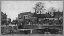 De Koemarkt omstreeks 1900. De Koemarktbrug met daarachter de stoomtram naar Rotterdam. Rechts de afgeknotte molen De Meiboom aan de Buitenhavenweg. In het midden café           Restaurant de Kroon. Links café Bellevue op de hoek van de Hoogstraat en Broersvest met rechts daarvan de afgeknotte molen De Batavier.