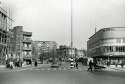 De Gerrit Verboonstraat, gezien in de richting van de Koemarkt. Links is nog net een deel van de in aanbouw zijnde Amsterdamsche Bank te zien (die werd geopend in juli           1955). Middenachter de flat Singelwijck met daar rechts voor hotel-café- restaurant