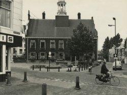 Het Stadhuis op de Grote Markt gezien vanaf de hoek met de Nieuwstraat in de richting van (rechts op de achtergrond) de Ooievaarssteeg. Op de markt is men bezig met het           aanbrengen van een fundament voor het (tijdelijk) plaatsen van een beeld t.g.v. het 700-jarig bestaan van Schiedam.