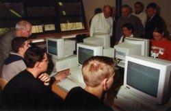 Genodigden in de op 23 maart 2000 geopende mediatheek van Scholengemeenschap Spieringshoek. Leerlingen demonstreren het gebruik van de leerlingencomputers. Staand v.l.n.r.:           docent B.W.G.van den Enden, docent A.H.G. Galjé, docent N.A.van Niekerk, Geheel rechts Tweede Kamer-lid Wim van der Camp (die de mediatheek opende).