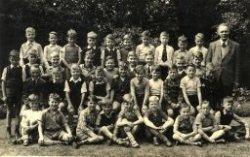 Tweede klas van de St. Thomasschool met onderwijzer A.J.van Rooijen. De foto is gemaakt in de Kloostertuin van het broederklooster aan de Warande. Een namenlijst is           beschikbaar bij de infobalie in de studiezaal.