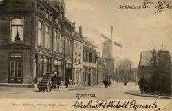 De Broersvest, gezien van een plek ter hoogte van de Buitenhavenweg, in de richting van het Emmaplein. Op de achtergrond in het midden molen De Eendracht. Geheel rechts,           deels achter de bomen, de stomp van molen De Batavier. Op de plaats van het hoge pand links staat nu het café 't Vierkantje.