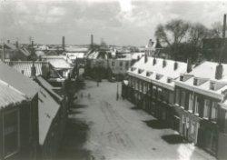 Gezicht vanaf de stomp van de Oostmolen staande op de hoek Broersvest en de Lange Kerkstraat, op de Broersvest. De bebouwing rechts staat tussen de Broersvest en het           zogeheten Koolas. Op de achtergrond rechts, net boven de besneeuwde daken, het voorgebouw van het Proveniershuis. Tussen en achter de bomen de contouren van het gebouw van de           Rijks-HBS.